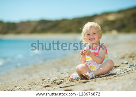 Happy baby girl playing on beach - stock photo