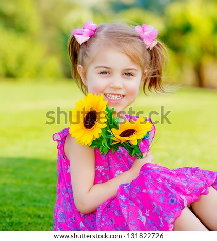 Happy baby girl playing outdoor, cute child holding fresh sunflower flowers, kid having fun in summer park, lovely smiling toddler portrait, enjoying nature of garden - stock photo