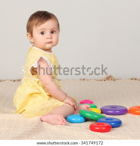 Happy baby girl playing with colorful toy  - stock photo