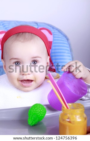 Happy baby girl sitting on high chair and eating lunch - stock photo