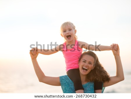 Happy baby girl sitting on shoulders of mother on beach in the evening - stock photo