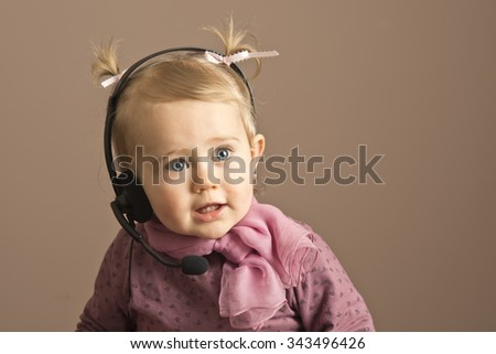 Happy baby girl talking on a headphones