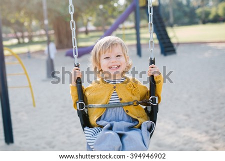 Happy baby girl toddler swinging in the park in the summer - stock photo