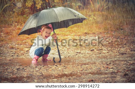 happy baby girl with an umbrella in the rain runs through the puddles playing on nature - stock photo