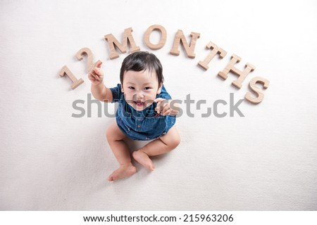 happy baby girl with hands thumbs up. 12 months. age concept. - stock photo