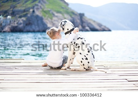 Happy baby girl with her dog on berth in summer