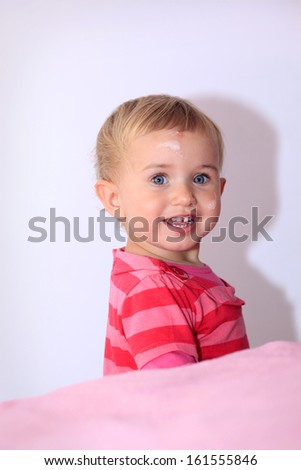 Happy baby girl with protective lotion on her face - stock photo