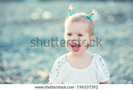 Happy baby girl with two tail hairstyle smiling and rejoicing in nature at sea on the beach - stock photo