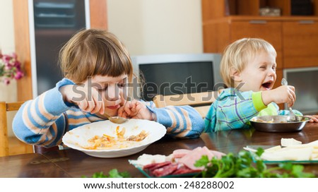 happy baby girls eating at wooden table in home interior - stock photo