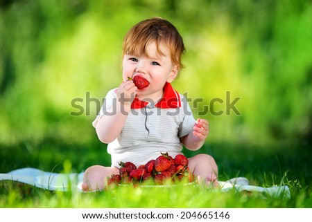 Happy baby have fun in the Park on a Sunny meadow with strawberry. Summer vacation concept. The emotions.