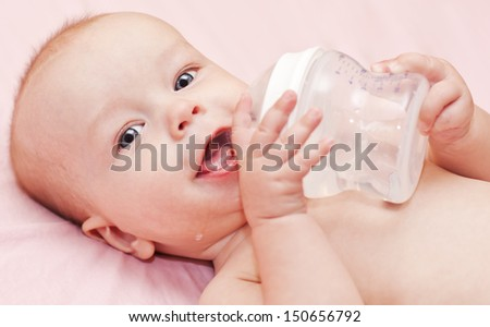 Happy baby holding a bottle and drink water looking at the camera - stock photo