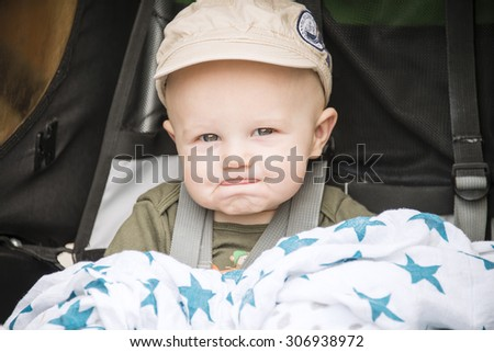 Happy Baby in a Cap Goes for a Bike Ride in a Carrier - stock photo