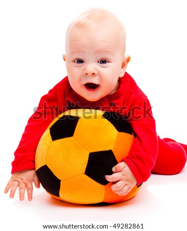 Happy baby in red lying on the soft soccer ball, over white - stock photo