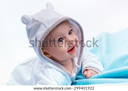Happy Baby in the hood on a blue blanket - stock photo