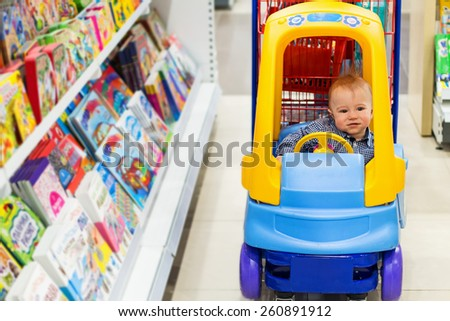 Happy baby in the little toy-car trolley in the kids shop in the bookstore department - stock photo