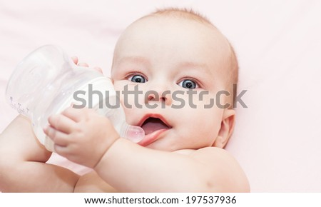 Happy baby is drinking water from a bottle - stock photo