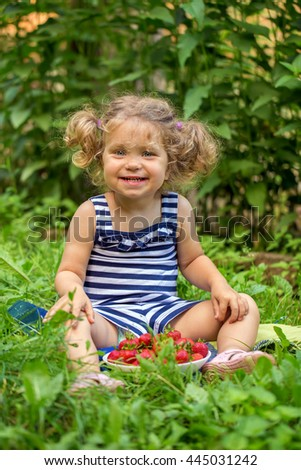 Happy baby kid with strawberries on green grass. Summer and healthy food concept.