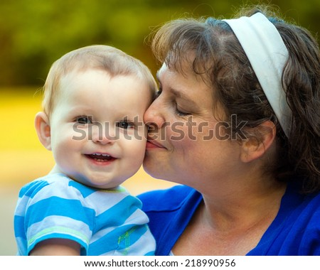 Happy baby kissed by mom - stock photo