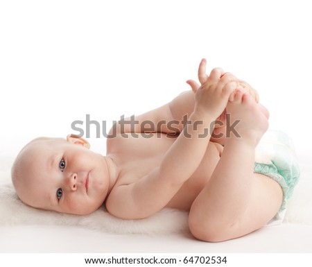 Happy baby laying on a soft rug - stock photo