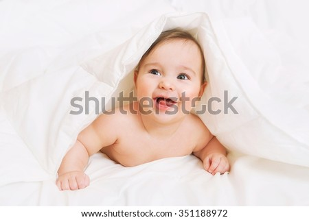 Happy Baby lies on bed under the blanket - stock photo