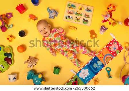 Happy baby lying back with toys - stock photo