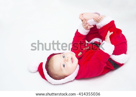 Happy baby lying on tummy wearing a red and white Christmas Santa suit, indoor shot - stock photo