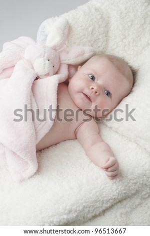 Happy baby lying on white furry blanket with pink toy rabbit, vertical layout with copy space.