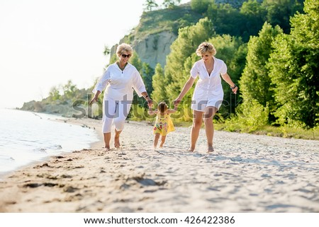 Happy baby, mother and grandmother together. baby, mother and grandmother with a walk on the beach in summer - stock photo