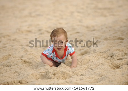 Happy baby on the beach crawling in the sand - stock photo