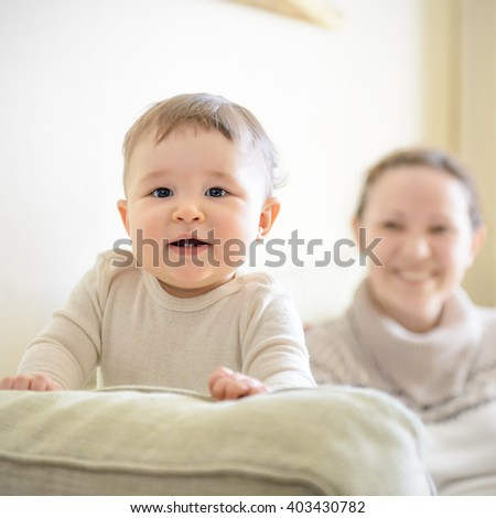 Happy baby plays with mother on the couch at home. Baby attentively looks.