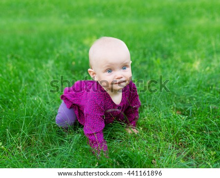 happy baby resting on the green grass. picnic