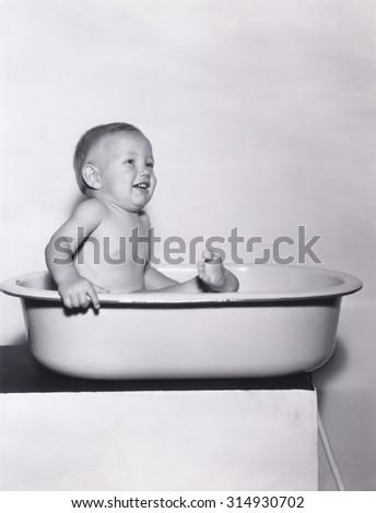 Happy baby sitting in bathtub - stock photo