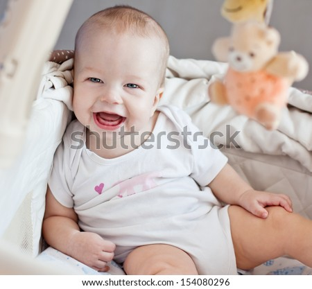 happy baby sitting in bed looking at the camera - stock photo