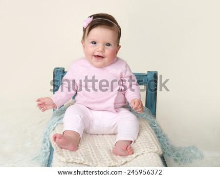 Happy baby sitting on Bed, milestones and development concept - stock photo