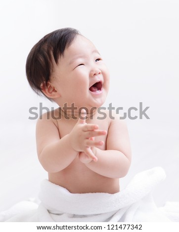 Happy baby smile and applaud and look empty copy space, asian child - stock photo