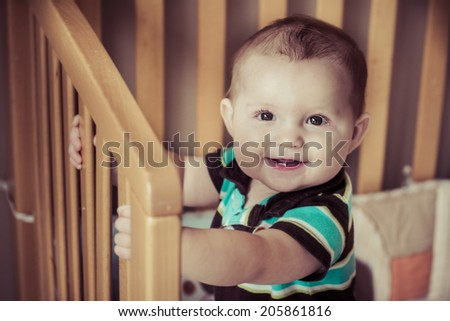 Happy baby standing up in his crib in image with vintage filter - stock photo