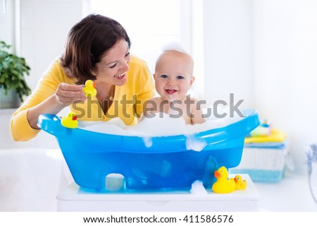 Happy baby taking a bath playing with foam bubbles. Mother washing little boy. Young child in a bathtub. Smiling kids in bathroom with toy duck. Mom bathing infant. Parent and kid play with water. - stock photo