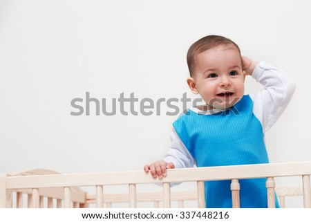 Happy baby toddler look at one side in the bed with hand on head on white background