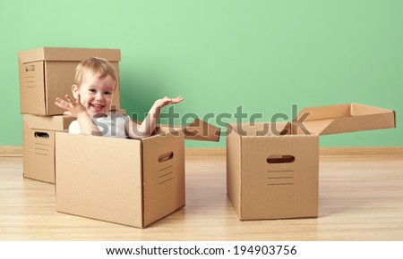 happy baby toddler sitting in a cardboard box empty room - stock photo