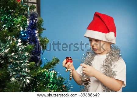 Happy baby wearing santa claus clothes with a new year gift - stock photo