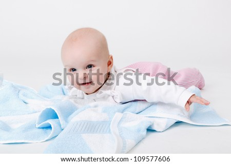 happy baby with a blue towel on the floor