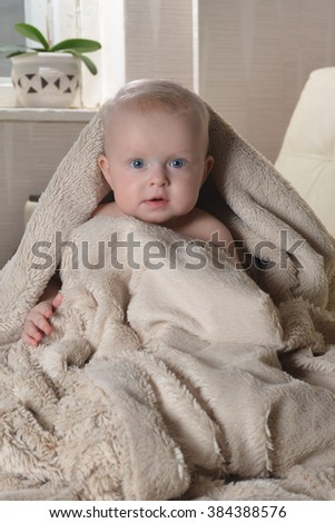 happy baby with a towel after the shower in bed at home - stock photo