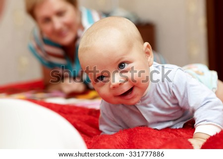 Happy baby with his grandmother on a bed - stock photo