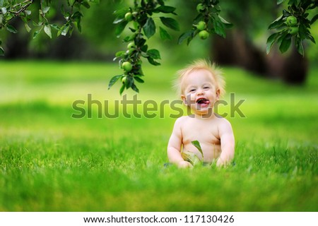 Happy baby with light and fluffy hair sitting on the grass and laughing. Summer and very warm. Happy smile. - stock photo