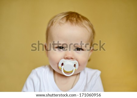 happy baby  with pacifier in soft selective focus - stock photo