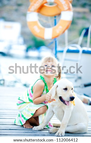 Happy babygirl with her dog on berth in summer