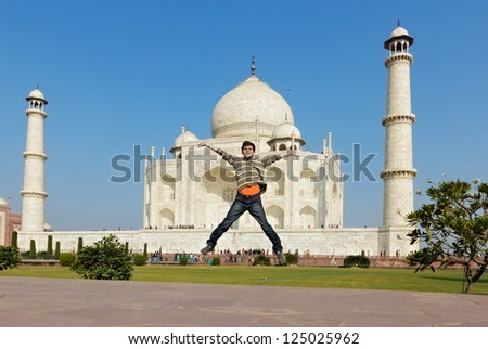 Happy backpacker jump. Taj Mahal on background. - stock photo