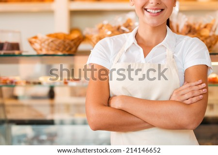 Happy baker. Close-up of beautiful young woman in apron keeping arms crossed while standing in bakery shop - stock photo