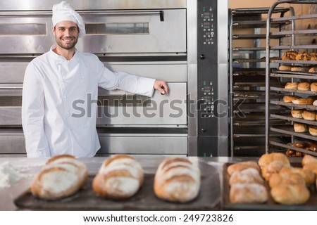 Happy baker leaning on professional oven at the bakery - stock photo