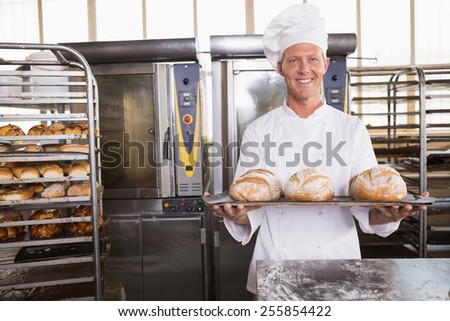 Happy baker showing tray of fresh bread in the kitchen of the bakery - stock photo